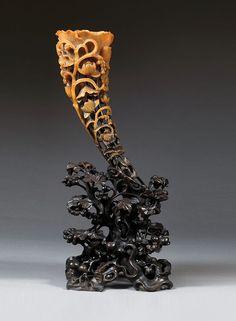 COUPE À LIBATION en corne de rhinocéros, l'extrémité de la coupe sculptée en forme d'une fleur de lotus, la corolle et la tige principale accostées de tiges secondaires portant fleurs et feuilles de lotus, l'ensemble reposant sur un socle en bois sculpté, ajouré et noirci, de belle patine, à décor d'un pêcher de longévité chargé de fruits.  (Petits accidents).  Chine, dynastie Qing, fin du XIXesiècle.