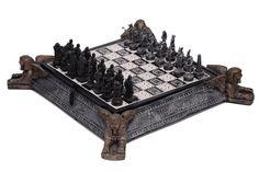 Tabuleiro de xadrez em madeira policromado em preto e branco, base de apoio representando 4 esfinges