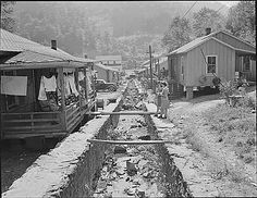 Double row houses; garbage and trash are disposed of in this meager stream of water;  there is a well and pump at each end of the row of houses. Panther Red Ash Coal Corporation,  Douglas Mine, Panther, McDowell County, West Virginia., 08/26/1946