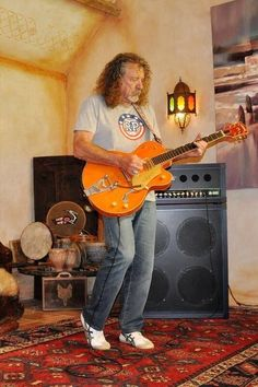 Robert Plant of Led Zeppelin playing guitar at home 2014