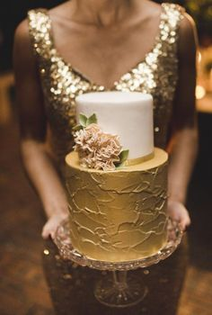 Beautiful bride or bridesmaid in sequined gold floor length gown holding the two tiered gold and ivory wedding cake...Rustic Luxe | WHITE Magazine