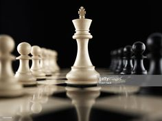 Stock Photo : White king chess piece facing opposition on chess board