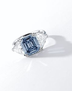 FINE FANCY VIVID BLUE DIAMOND AND DIAMOND RING Centring on an emerald-cut fancy vivid blue diamond weighing 3.32 carats, flanked by two trilliant-cut diamonds together weighing approximately 2.00 carats, mounted in 18 karat white gold. Ring size: 6