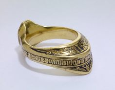 Gold signet-ring; in form of bow-ring. Octagonal bezel is engraved in intaglio with shield of arms: per bend, column and three bends, for Donati(?), surmounted by crest and helm with mantling. Engraved with inscription; pearled border; nielloed reserved inscription around hoop with rosettes between several words. Extended back of ring decorated with column. Italy (Venice), 14th century.