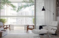A luz natural entra suave na sala. Os raios de sol são filtrados pela persiana branca, com acabamento de xale de linho. Todo ambiente interno também é claro, inclusive o piso. Projeto da arquiteta Paula Magnani