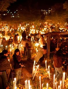 People standing amongst graves decorated with flowers and lit candles, and spent all night at a cemetery in Oaxacaç.