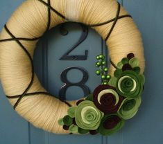 This wreath is wrapped in a sweet yellow with brown & green criss-crossing, a collection of green and brown felt blooms and a sprig of berries!  Perfect