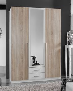 Mit dem Drehtürenschrank SKATE entscheiden Sie sich für einen eindrucksvollen Kleiderschrank, der Ihnen mit Stil und Funktionalität zur Seite steht. Optisch begeistert dieser mit seinem freundlichen Alpinweiß, den schönen Kontrast dazu bilden die drei Drehtüren im gemütlichen Eiche Sägerau Dekor. Auf der mittleren Tür ist zudem ein Kristallspiegel befestigt, mit dem Sie Ihr Outfit sofort im Blick haben. Armoire, Outfit, Furniture, Home Decor, Wardrobe With Mirror, Clothes Stand, Outfits, Decoration Home, Room Decor