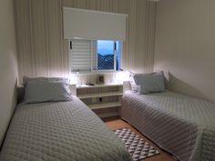 Dormitório de hóspedes em tons de cinza no papel de parede e colcha dão o toque acolhedor.