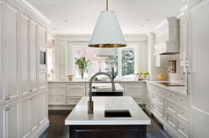 Stunning kitchen features white shaker cabinets paired with white quartz countertops and subway ...