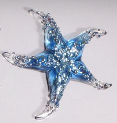 Baby Blue Starfish Weight by Gina Lunn. Beautiful starfish, hand sculpted in glass with silver accents on the surface, creating a raised bumpy texture.