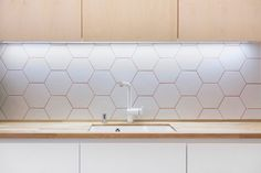 White hexagonal tiles line the back wall of the kitchen, with pinkish grouting complementing the wooden cupboards and surfaces.