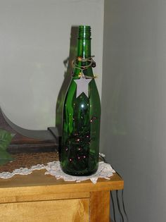 Sale Item***********Up Cycled Lighted Green Glass Bottle with Purple Lights, Wire Garland with Tin Star. $14