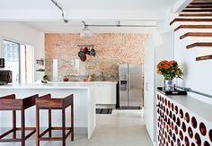 A cozinha desta casa de vila é o centro das atenções. Em frente à pia, uma placa de vidro protege a parede da sujeira. No canto direito da foto, uma adega feita com tijolos cilíndricos de cerâmica. Projeto da arquiteta Rachel Nakata  Lufe Gomes / Casa e Jardim