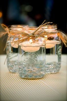 floating candles with cheap bows. great wedding idea