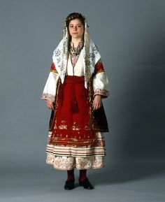 "At Kefalovrysso, Argolid, Peloponnese we encounter costume ""ensembles"" similar to those of Arcadia, Peloponnese. They are characterized by the combination of chemise, dress, apron and girdle with a black outer sleeveless short coat the ""sigouni"" or ""yiourda""."