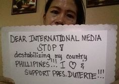 Filipino woman holding a sign to international media asking them to stop 'destabilizing my country Philippines'