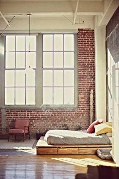 A bed under huge windows which let in lots of sun, and exposed brick.  I would die if my apartment looked like this.
