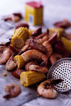 1 gallon water  2 tablespoons crab boil or Old Bay seasoning  2 tablespoons salt  2 small cloves garlic, minced  12 small new potatoes, scrubbed  1 1⁄2 pounds andouille or smoked sausage, halved lengthwise and sliced crosswise into 1⁄2-inch-thick pieces  6 ears corn, cleaned and each cut crosswise into 3 pieces  3 pounds medium shrimp