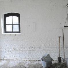 Location de lieu insolite pour shooting photo : une étable avec mur de briques blanchies et sol brique.