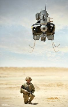 A soldier watches as a Tarantula Hawk (T-Hawk) Micro Remote Piloted Air System (RPAS) hovers over the desert in Afghanistan.