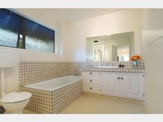 Bathroom of 2 bedroom brick and cedar 1977 home @ Kelvin Road, Remuera. Original - large beige-brown tiled bath, part wall and benchtop and white colonial style cupboards, swirled window glass.  (in Nov 2014)