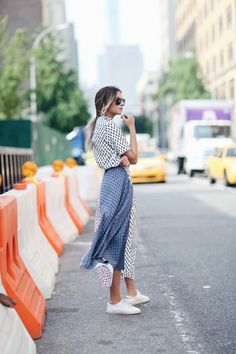 Danielle Bernstein of We Wore What wears a printed shirtdress with sleek white sneakers and aviators