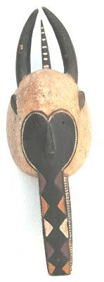"Baule (Baoule) Mask, wood, oval face with white pigment around a heart-shaped black inner, leading to protruding animal snout. Two curved horns bracket a single pointed spur. 35"" high US$650"