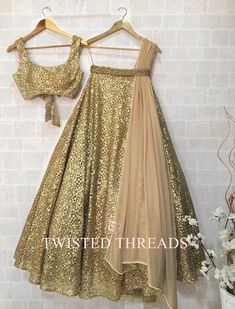 Gold Lehenga Twisted Threads. A golden net lehenga with tikki work. It comes with a matching gold blouse and a beige georgette dupatta.
