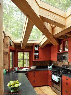 Cuisine rouge avec poutres et parquet bois dans véranda