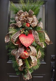 Valentine Wreath - Valentines Swag - Valentine Heart Swag - Leopard Valentines Wreath This swag is RESERVED for Debbie. Dress your door with this flirty leopard vertical swag/wreath for Valentines Day. I used over 40 feet of gorgeous leopard print ribbon in this design. I just love the way the ribbon mimics a beautiful dress. The heart is removable, so you can enjoy it through the Christmas season too. This is a very large swag! 42 tall by 20 Wide (at widest point) & 9 Deep I measure f...