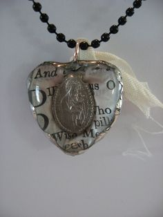 Piece of an old tattered prayer book, rosary medal made into a soldered jewelry charm necklace.