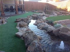 Golf Greens Texas's artificial turf installed in back yard around a water feature.