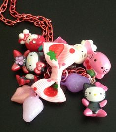 Handmade pink hued Hello Kitty charmed necklace.  Charms include 5 Sanrio Hello Kitty Charms, 2 strawberries, 2 kissy lips, 2 glass pink leaves, and 1  Pink Jingle bell Hello Kitty, topped off with a