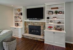 Setback fireplace with cabinets on sides. But we wouldn't have the raised hearth or the built in shelves--do floating shelves instead.