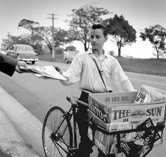 Newspaper boy on bicycle, with The Sun and Daily Mirror newspapers. Max Dupain photo, 1963.
