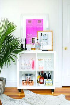 White bookshelf used as home bar with small palm tree and vibrant purple artwork