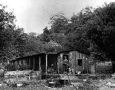 Leonard Arbogast stands on the porch of his wooden cabin. He holds a shotgun and stands next to his dog. His wife and baby can be seen through the window of the cabin. Big Run Creek, near mouth of Sawmill River, Monongahela National Forest, West Virginia.