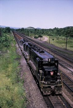 PRR train just west of Bellwood, Blair County on June 26, 1965. PRR engines 2245, 2350, and 2282 are pulling a 95 car westbound ore train with N8 caboose 478170. Photo taken from the Rte 483 bridge.