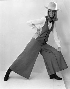 Source: http://www.vogue.it/en/encyclo/designers/q/mary-quant-  Mary Quant in wide legged trouser suit, non-sleeved waist coat with cowboy hat and heeled winklepickers in 1967.