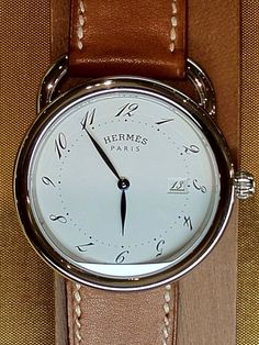 HERMÈS PARIS~ MONTRE ARCEAU ~ This watch has become a classic; round with Arabic numerals swirling around the dial. The top stitched luggage leather strap is looped through an equestrian motif loop,,a reference to Hermès' beginnings as a saddle maker.