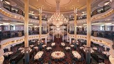 restaurante do navio; foco no pé direito altão, e na baranguisse do lustre e do carpete