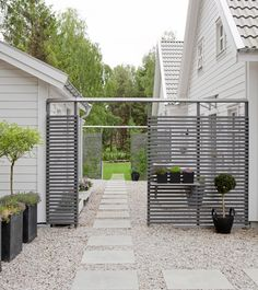 Uterum Trivselhus.  Nice modern gravel patio area with gray fence,