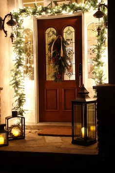 Greenery wrapped in white lights, candle lanterns on porch.