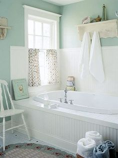 Cottage Bathtub Design:  A wide ledge is a good way to create a comfortable and safe means to get into a deep bathtub. It also creates an attractive and highly functional architectural detail in even the smallest bathroom. Here the apron in front of the tub matches the wood panels surrounding it to create an integrated look.   ALSO:  LOVE THAT RUG IN FRONT OF THE TUB.