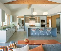 Blue, orange, + white colors bring out the playfulness of this open plan #midcentury #modern #kitchen