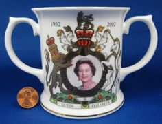 This is a British royal memorabilia souvenir loving cup to commemorate the Golden Jubilee in 2002 of the 50 year reign of Queen Elizabteth II of England. The English bone china 2 handled mug was made
