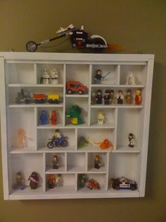 """LEGOS!  Bought the shadow box at a garage sale for a few dollars.  Spray painted it white, replaced glass w/ plexi (safer for kids).  Added mini-figures and hung on wall of """"LEGO Room.""""   Son displays the LEGO Advent calendar models during December.  SO CUTE."""