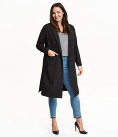 Pudderrosa. Lang, lige jakke i vævet kvalitet. Den har en enkelt knap, lommer foran og slids i siderne. Uden for.