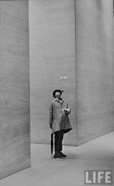 Jacques Tati looking at the high ceiling of an office lobby, New York, October 1958 by Yale Joel